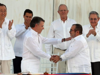 Colombia's President Juan Manuel Santos, front left, and the top commander of the Revolutionary Armed Forces of Colombia (FARC) Rodrigo Londono, known by the alias Timochenko, shake hands after signing the peace agreement between Colombia's government and the FARC to end 50 years of war